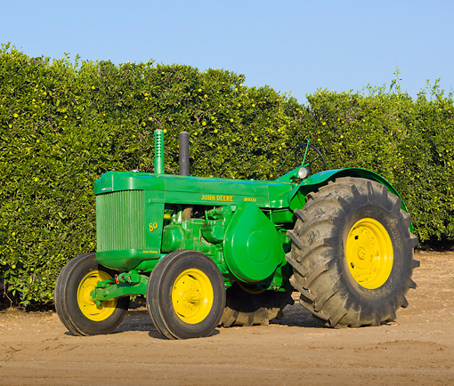 TRA 01 RK0167 01 © Kimball Stock 1955 John Deere 80 Green And Yellow 3/4 Side View On Dirt By Shrubs