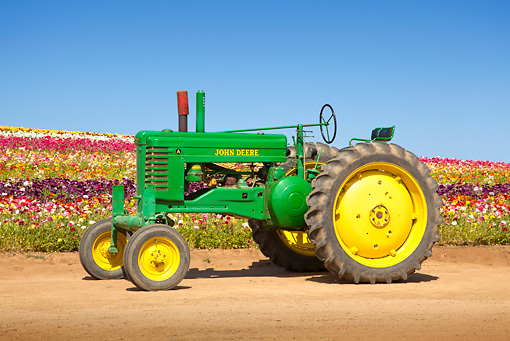 TRA 01 RK0175 01 © Kimball Stock 1949 John Deere A Green And Yellow Profile View On Dirt By Field Of Flowers