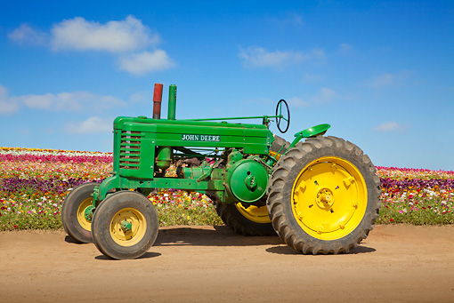 TRA 01 RK0178 01 © Kimball Stock 1940 John Deere Antique Tractor Green And Yellow Profile View On Dirt By Field Of Flowers