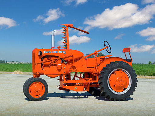 TRA 01 RK0181 01 © Kimball Stock 1946 Allis-Chalmers C Tractor Orange Profile View On Pavement By Farm