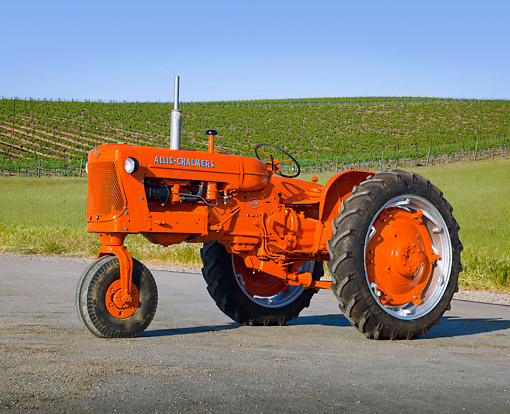 TRA 01 RK0182 01 © Kimball Stock 1958 Allis-Chalmers D-14 Tractor Orange 3/4 Front View On Pavement By Vineyard