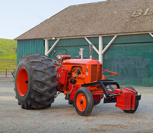 TRA 01 RK0192 01 © Kimball Stock 1948 Case DC Tractor Orange 3/4 Front View On Pavement By Barn