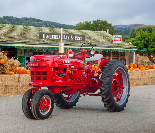 TRA 01 RK0200 01 © Kimball Stock 1944 Farmall H Tractor Red With 27V Mower 3/4 Front View On Pavement By Feed Store And Pumpkins