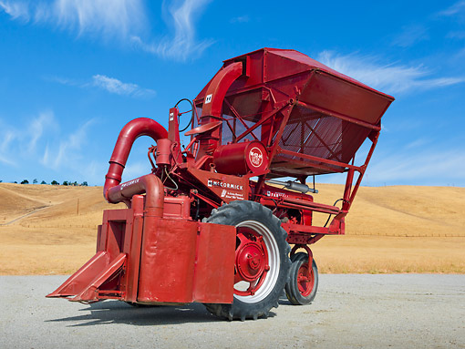 TRA 01 RK0204 01 © Kimball Stock 1944 Farmall Tractor With 1952 McCormick Cotton Picker Red 3/4 Side View On Pavement By Dry Grass