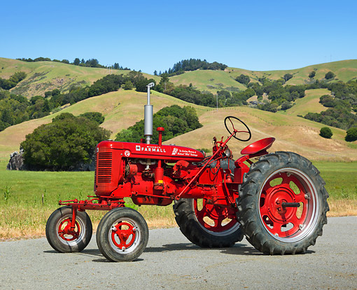 TRA 01 RK0207 01 © Kimball Stock 1953 Farmall Super C Tractor Red 3/4 Side View On Pavement By Grassy Hills