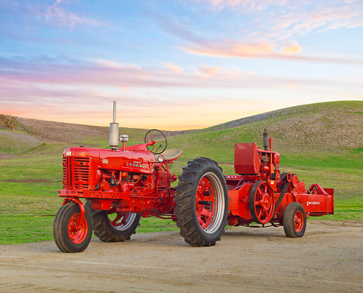 TRA 01 RK0208 01 © Kimball Stock 1955 Farmall 300 Tractor Red And 1954 McCormick 55W 3/4 Side View On Dirt By Grassy Hills At Dusk