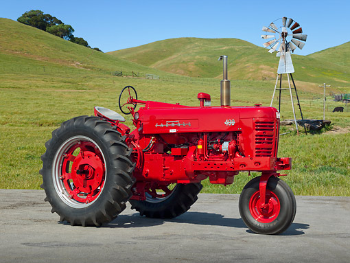 TRA 01 RK0211 01 © Kimball Stock 1955 Farmall 400 Tractor Red 3/4 Side View On Pavement Grassy Hills And Windmill