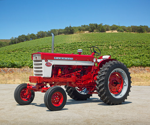 TRA 01 RK0214 01 © Kimball Stock 1958 Farmall 560 Tractor Red And White 3/4 Side View On Gravel By Crops