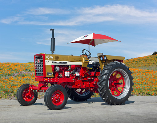 TRA 01 RK0218 01 © Kimball Stock 1970 Farmall 544 Tractor Red With Gold Demonstrator 3/4 Side View On Pavement By Wildflowers