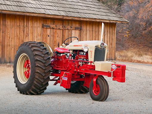 TRA 01 RK0220 01 © Kimball Stock 1958 Ford 950 Tractor Red 3/4 Side View On Gravel By Wooden Shed
