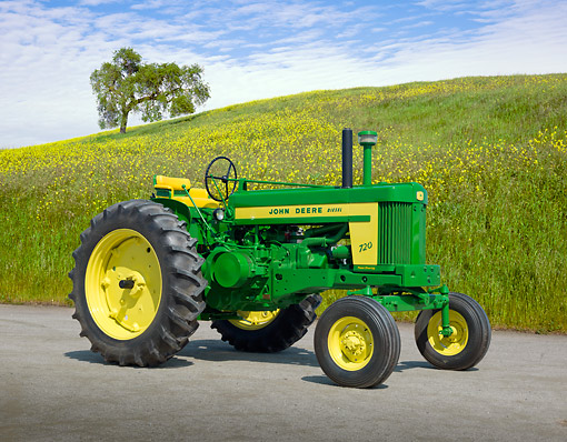TRA 01 RK0229 01 © Kimball Stock 1957 John Deere 720 Tractor Green And Yellow 3/4 Side View On Pavement By Field Of Wildflowers