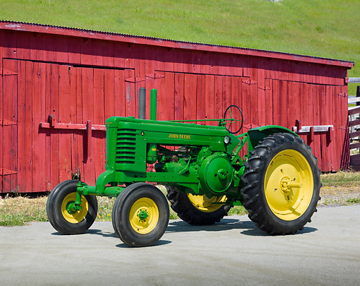 TRA 01 RK0230 01 © Kimball Stock 1940 John Deere Tractor Green And Yellow 3/4 Side View On Pavement By Red Barn