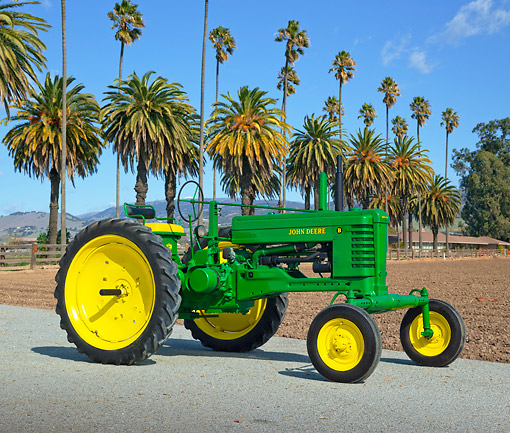 TRA 01 RK0241 01 © Kimball Stock 1950 John Deere B Tractor Green And Yellow 3/4 Side View On Pavement By Palm Trees