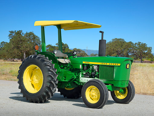 TRA 01 RK0246 01 © Kimball Stock 1979 John Deere 1020 Tractor Green And Yellow 3/4 Side View On Pavement By Dry Grass
