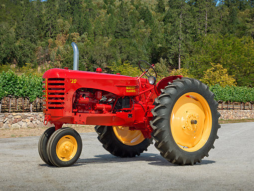 TRA 01 RK0255 01 © Kimball Stock 1951 Massey-Harris 30 GR Tractor Red And Yellow 3/4 Side View On Gravel By Trees