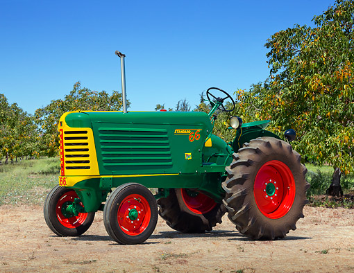 TRA 01 RK0264 01 © Kimball Stock 1949 Oliver 66 Standard Tractor Green, Yellow And Red 3/4 Side View On Dirt By Trees