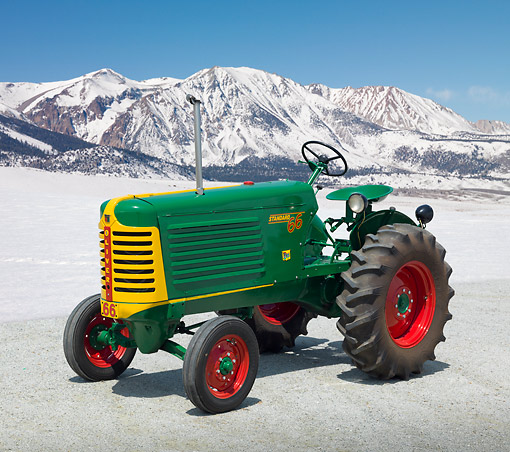 TRA 01 RK0265 01 © Kimball Stock 1949 Oliver 66 Standard Tractor Green, Yellow And Red 3/4 Side View On Gravel By Snow Covered Mountains