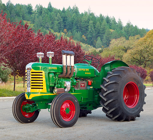 TRA 01 RK0273 01 © Kimball Stock 1957 Oliver Super 99 Tractor Green, Yellow And Red 3/4 Side View On Gravel By Autumn Trees