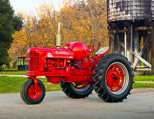 TRA 01 RK0276 01 © Kimball Stock 1954 Farmall Super MTA Tractor Red 3/4 Side View On Gravel By Water Tower And Autumn Trees