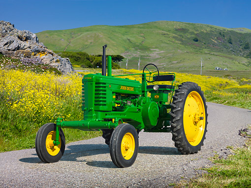 TRA 01 RK0278 01 © Kimball Stock 1948 John Deere BW Tractor Green And Yellow 3/4 Front View On Pavement By Yellow Wildflowers