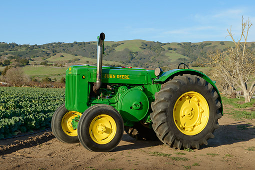 TRA 01 RK0284 01 © Kimball Stock 1980 John Deere Style D Tractor Green And Yellow 3/4 Side View On Dirt At Farm