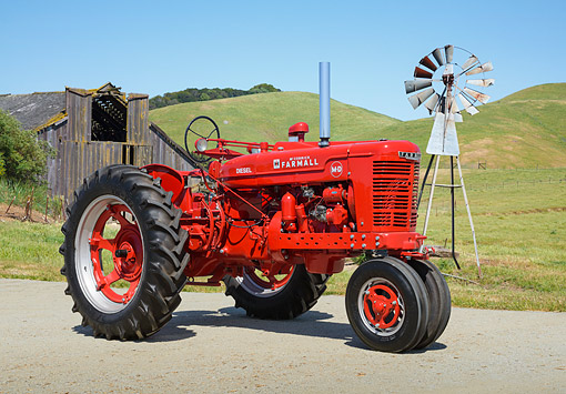 TRA 01 RK0291 01 © Kimball Stock 1938 Farmall M Diesel 2150 IH Red 3/4 Side View On Pavement By Old Windmill