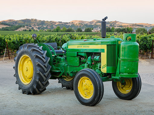 TRA 01 RK0293 01 © Kimball Stock 1956 John Deere 420 Green And Yellow 3/4 Side View On Gravel By Vineyard