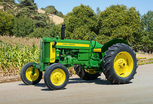 TRA 01 RK0294 01 © Kimball Stock 1957 John Deere 420 Green And Yellow 3/4 Side View On Pavement By Cornfield And Trees