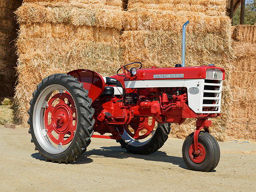 TRA 01 RK0300 01 © Kimball Stock 1961 International Farmall 240 Red 3/4 Side View On Dirt By Hay Bales