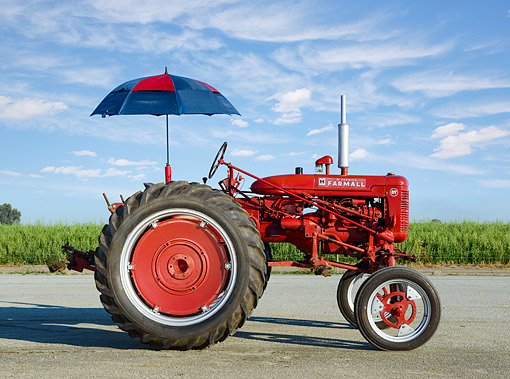 TRA 01 RK0301 01 © Kimball Stock 1953 IH Super AV Red Profile View On Pavement By Cornfield