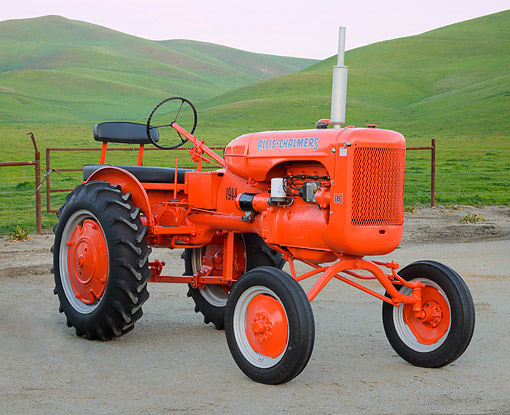 TRA 01 RK0305 01 © Kimball Stock 1944 Allis-Chalmers B Orange 3/4 Front View On Pavement By Grassy Hills