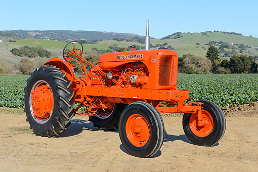 TRA 01 RK0307 01 © Kimball Stock 1951 Allis-Chalmers WD Tractor Orange 3/4 Front View On Dirt By Farm Crops