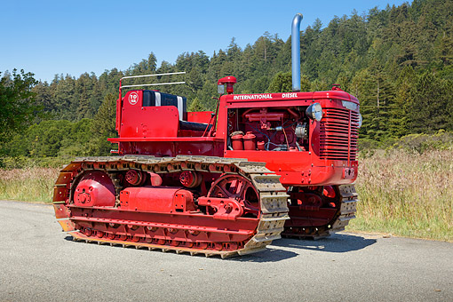 TRA 01 RK0310 01 © Kimball Stock 1950 International TD-14A Tractor Red 3/4 Side View On Pavement By Evergreen Trees