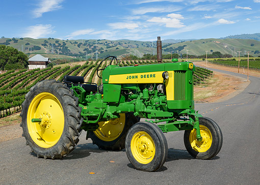 TRA 01 RK0311 01 © Kimball Stock 1985 John Deere 430 Tractor Green And Yellow 3/4 Side View On Road By Vineyard