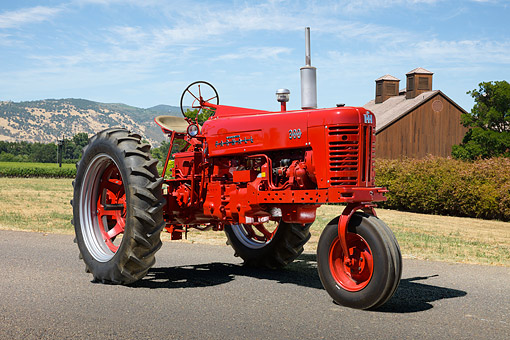 TRA 01 RK0312 01 © Kimball Stock 1954 McCormick Farmall 300 Tractor Red 3/4 Front View On Pavement By Barn