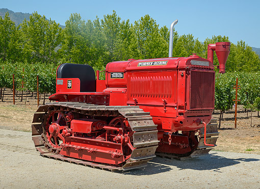 TRA 01 RK0313 01 © Kimball Stock 1935 McCormick-Deering T-20 Tractor Red 3/4 Side View On Gravel By Vineyard