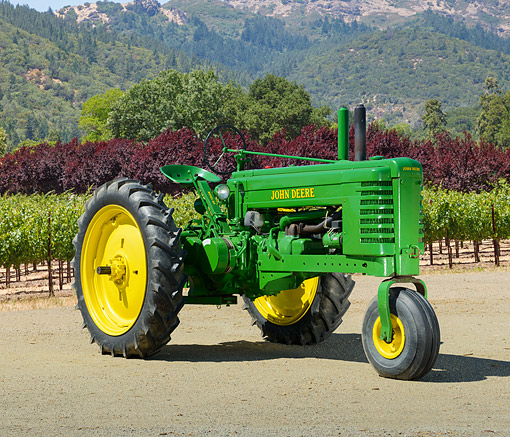 TRA 01 RK0315 01 © Kimball Stock 1940 John Deere Model BN Tractor Green And Yellow 3/4 Front View On Dirt By Vineyard
