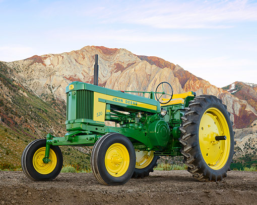 TRA 01 RK0318 01 © Kimball Stock 1954 John Deere 520 Tractor Green And Yellow 3/4 Front View On Dirt By Mountains