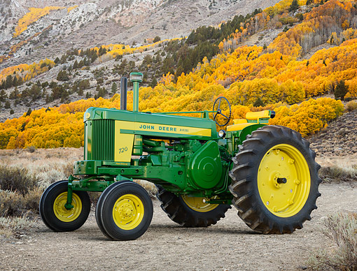 TRA 01 RK0320 01 © Kimball Stock 1957 John Deere 720 Tractor Green And Yellow 3/4 Side View On Gravel By Mountains
