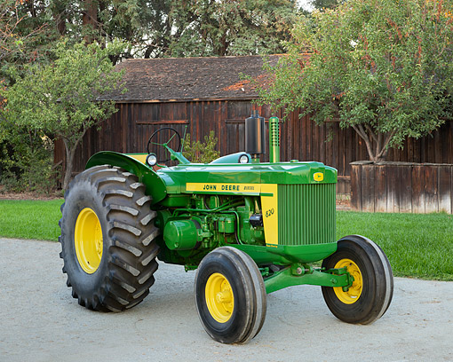 TRA 01 RK0321 01 © Kimball Stock 1957 John Deere 820 Tractor Green And Yellow 3/4 Front View On Gravel By Wooden Shed
