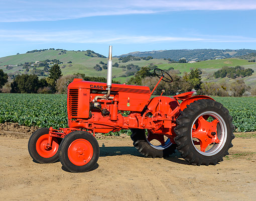 TRA 01 RK0323 01 © Kimball Stock 1946 Case VAC Tractor Flambeou Red 3/4 Side View On Dirt By Crops