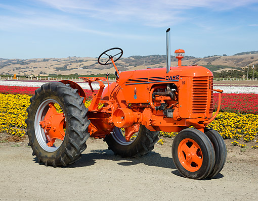 TRA 01 RK0324 01 © Kimball Stock 1941 Case V Tractor Orange 3/4 Front View On Gravel By Field Of Flowers