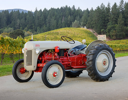 TRA 01 RK0329 01 © Kimball Stock 1948 Ford 8N-V8 Tractor Gray And Red 3/4 Side View On Pavement By Vineyard