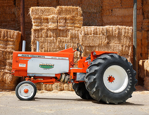 TRA 01 RK0332 01 © Kimball Stock 1964 Allis-Chalmers XT One-Ninety Tractor Orange Profile View On Gravel By Hay Bales