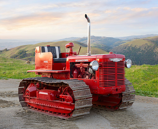 TRA 01 RK0335 01 © Kimball Stock 1940 International TD-6 Tractor Red 3/4 Front View On Wet Gravel By Grassy Hills