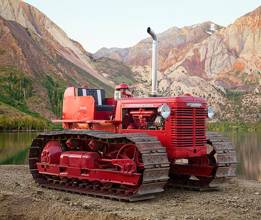 TRA 01 RK0336 01 © Kimball Stock 1950 International TD-9 Tractor Red 3/4 Front View On Dirt By Lake And Mountains