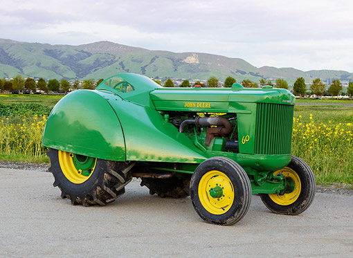 TRA 01 RK0341 01 © Kimball Stock 1954 John Deere 60 Tractor Green And Yellow 3/4 Side View On Gravel By Wildflowers