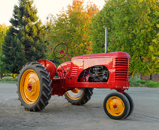 TRA 01 RK0343 01 © Kimball Stock 1941 Massey-Harris 81 Tractor Red 3/4 Side View On Gravel By Trees