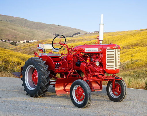 TRA 01 RK0345 01 © Kimball Stock 1957 McCormick Farmall 130 Tractor Red 3/4 Front View On Gravel By Wildflowers