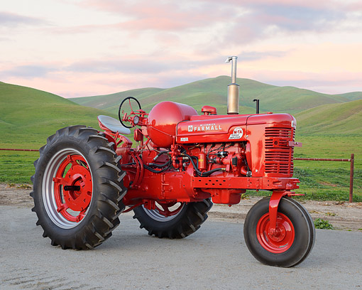 TRA 01 RK0346 01 © Kimball Stock 1952 McCormick Farmall M-TA Tractor Red 3/4 Side View On Gravel By Grassy Hills
